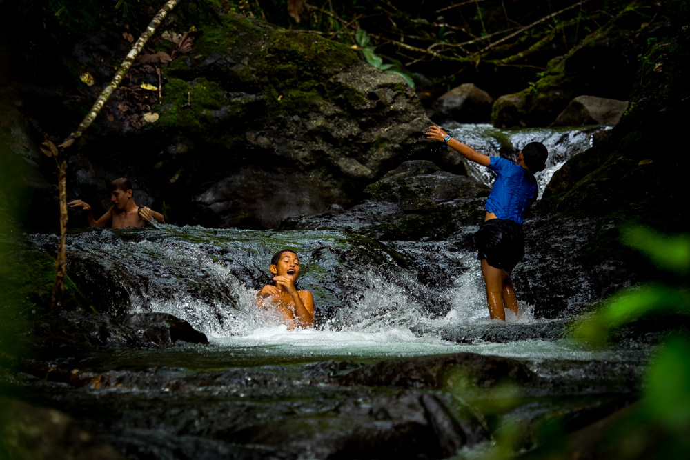 Kids playing in the river after hiking in the Papenoo Valley, Tahiti, French Polynesia
